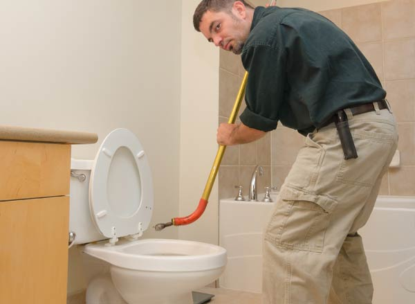 Snaking a clogged toilet with a closet auger